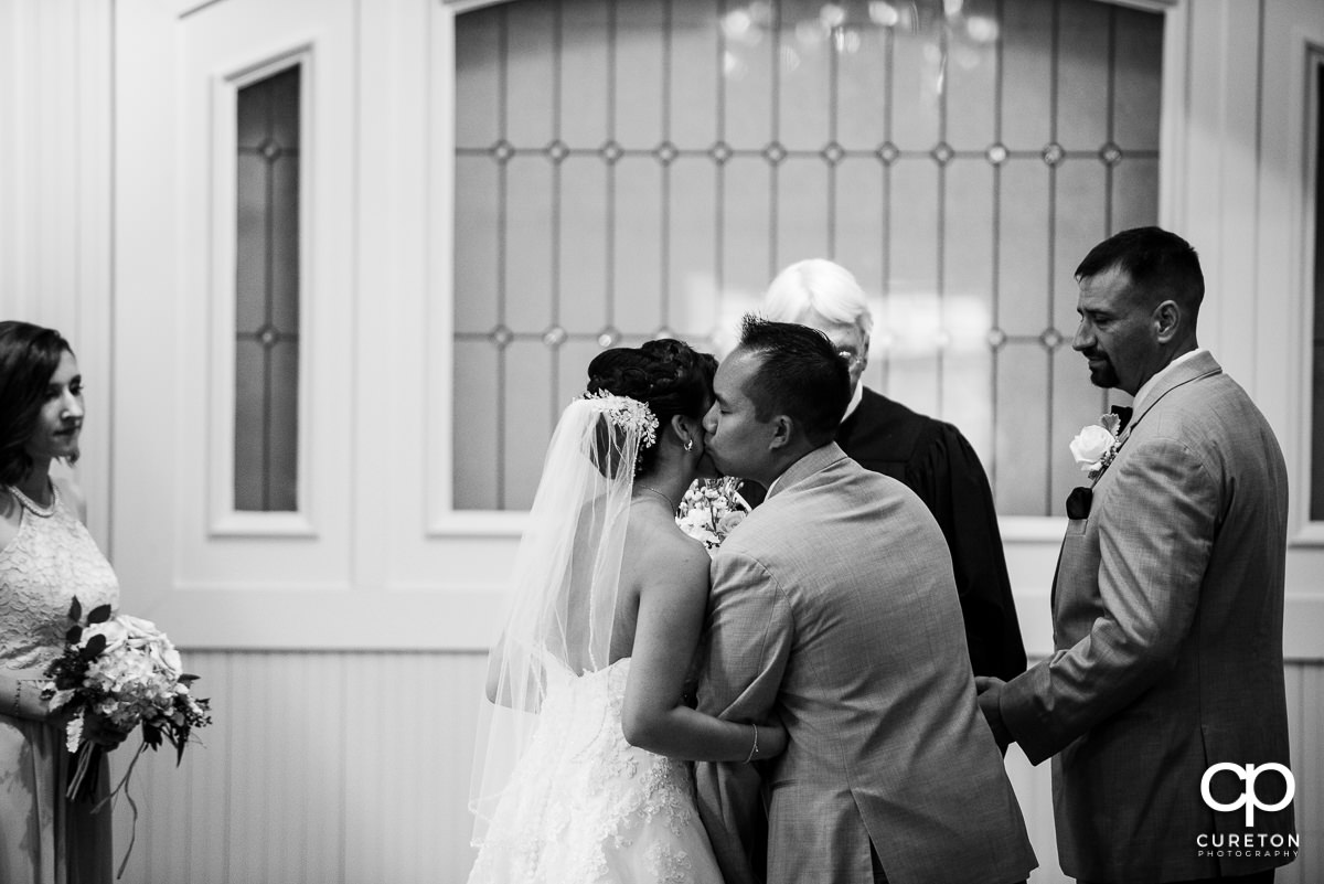 Bride's brother kissing his sister on the cheek at her wedding ceremony.