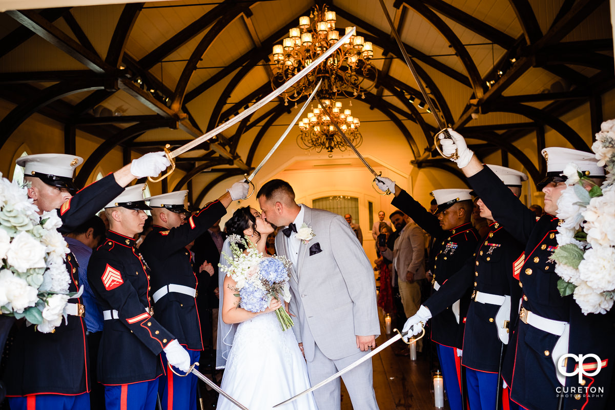Bride and groom kissing while leaving their Tybee Island Chapel Wedding through a Marine saber arch.