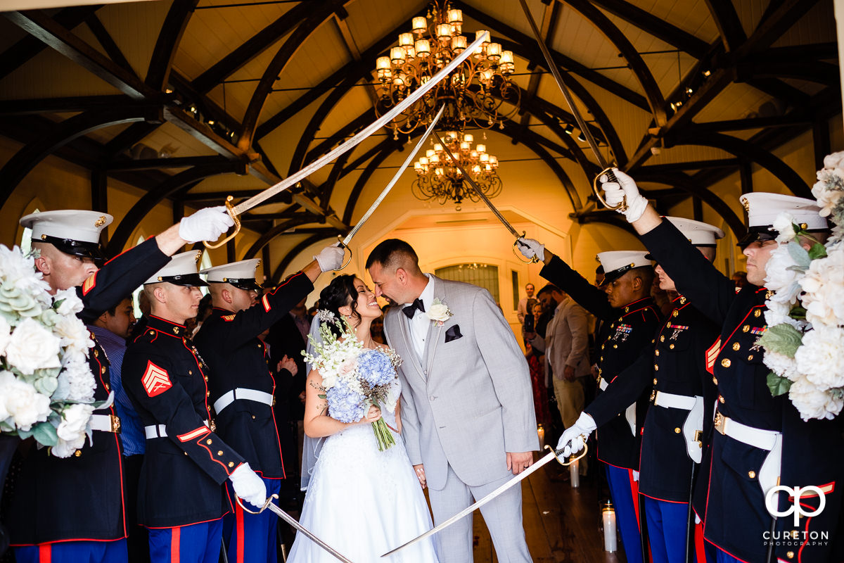 Bride and groom smiling at each other underneath a Marine saber arch at their coastal wedding ceremony.