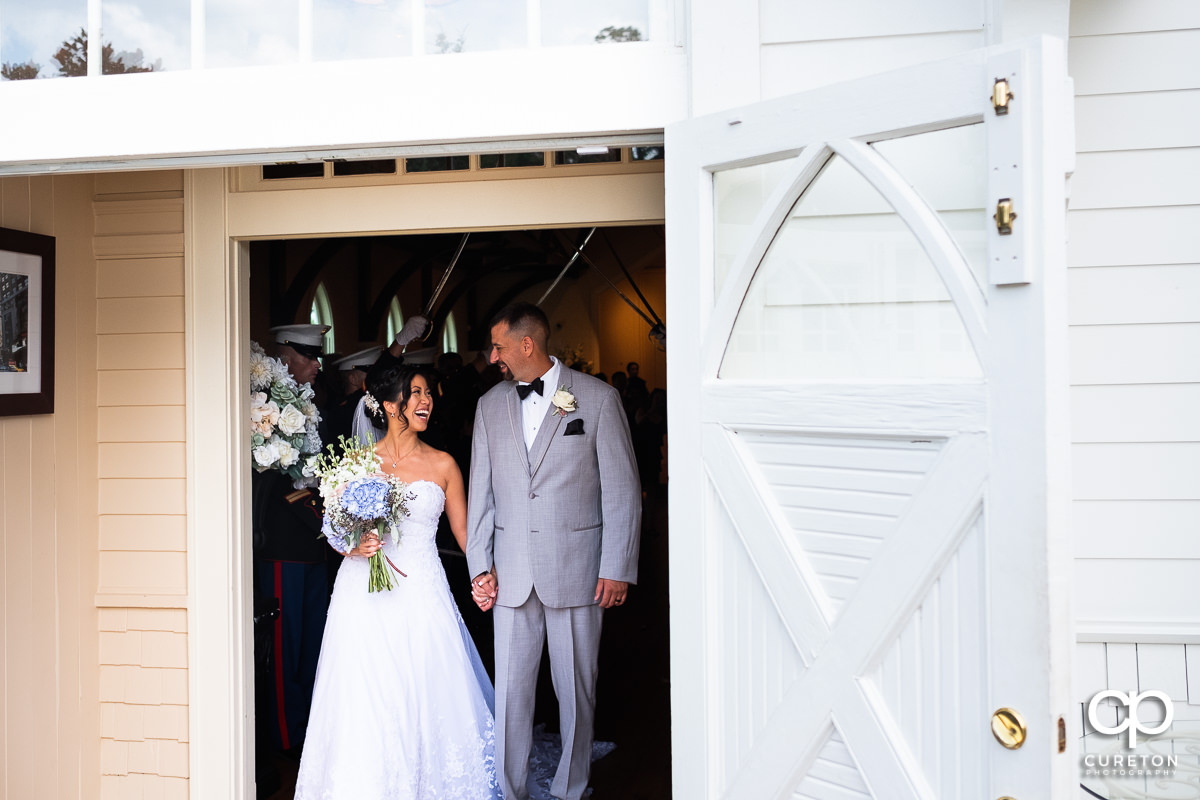 Bride and groom smiling and laughing leaving their Tybee Island wedding ceremony.