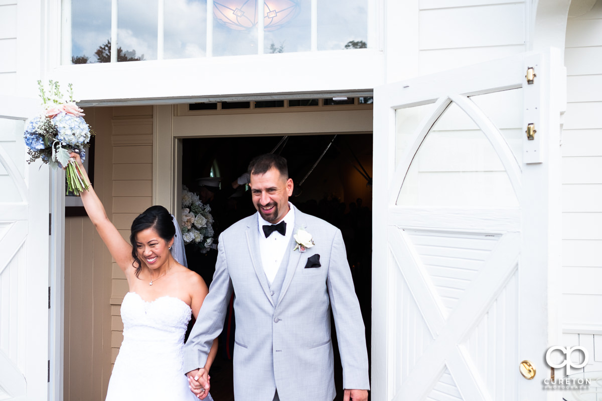 Bride and groom smiling with hands in the air leaving their Tybee Island wedding ceremony.