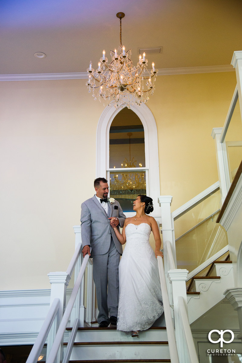Bride and groom making a grand entrance down the staircase at the Tybee Island Chapel reception.