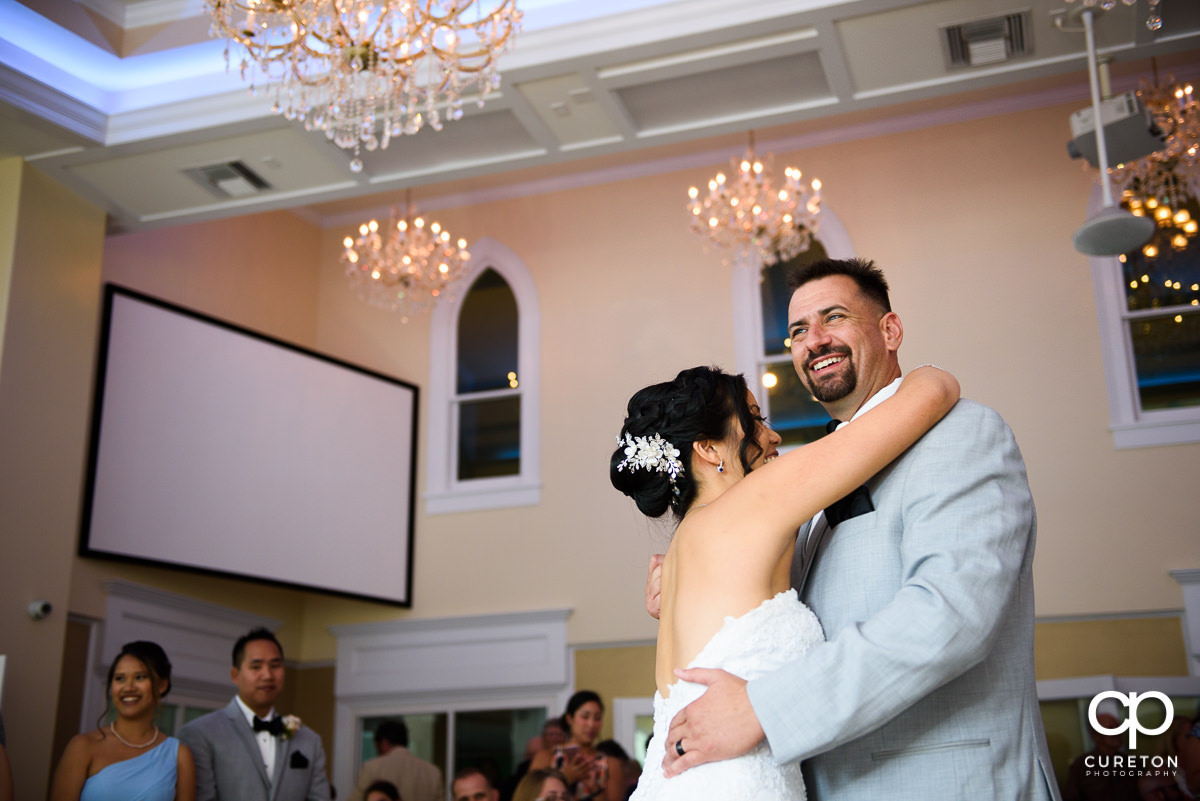 Groom smiling during their first dance at the wedding reception.