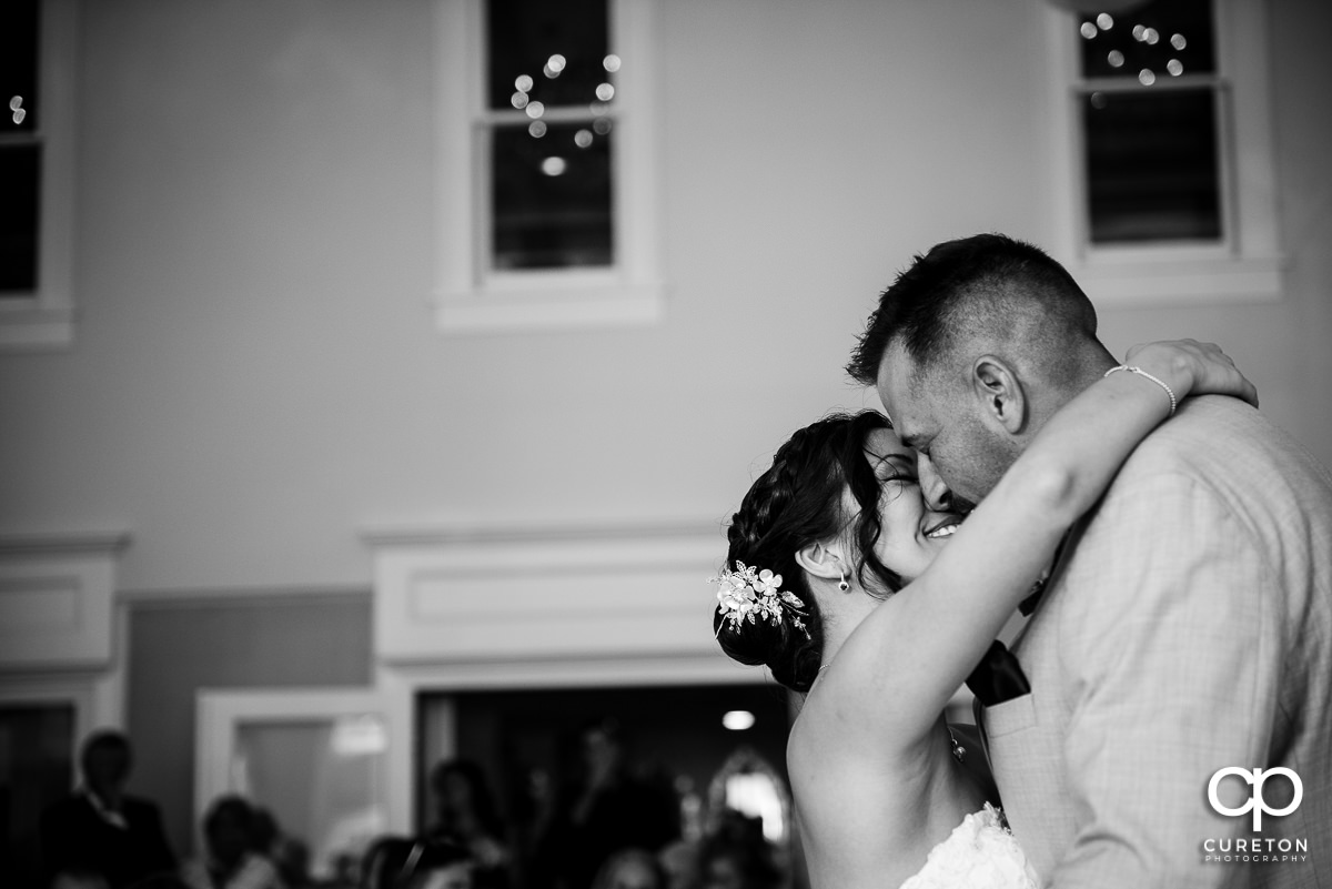 Bride kissing her groom during their first dance.