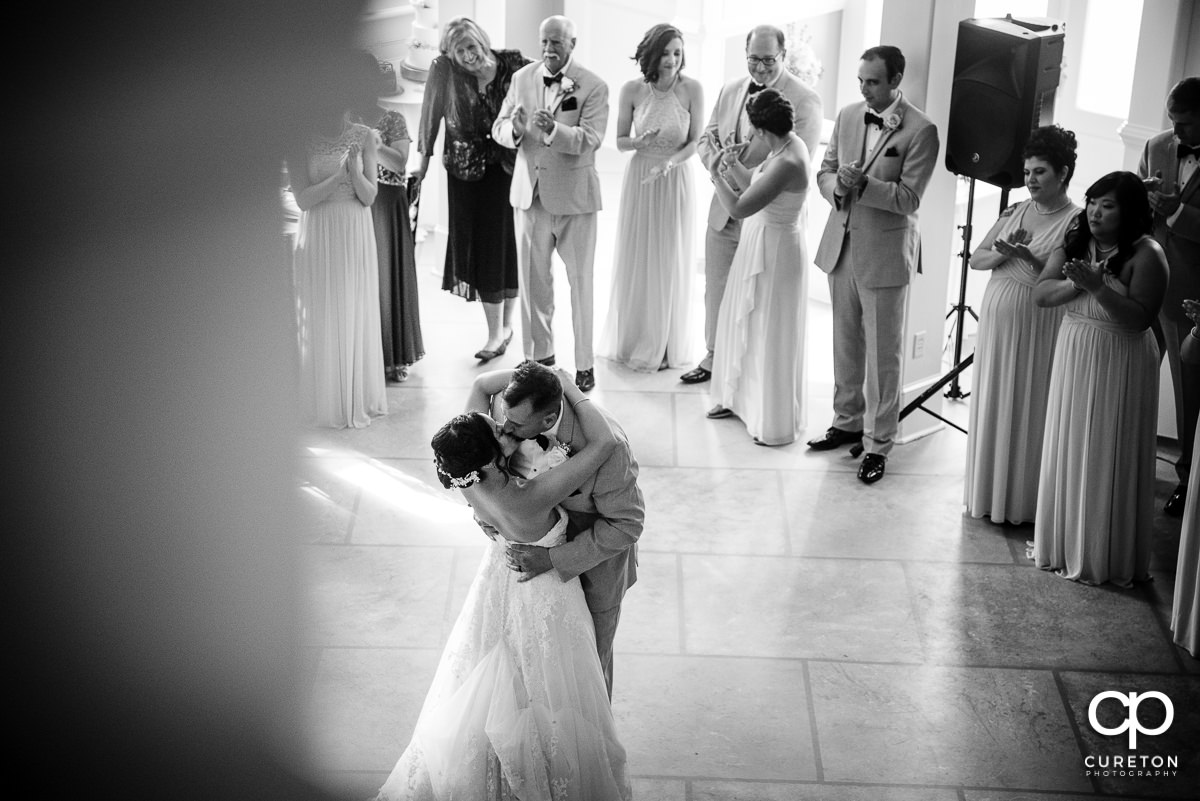 Groom kissing his bride after their first dance.