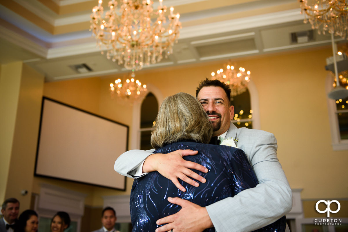 Groom hugging his mom as the share a dance at the wedding reception.