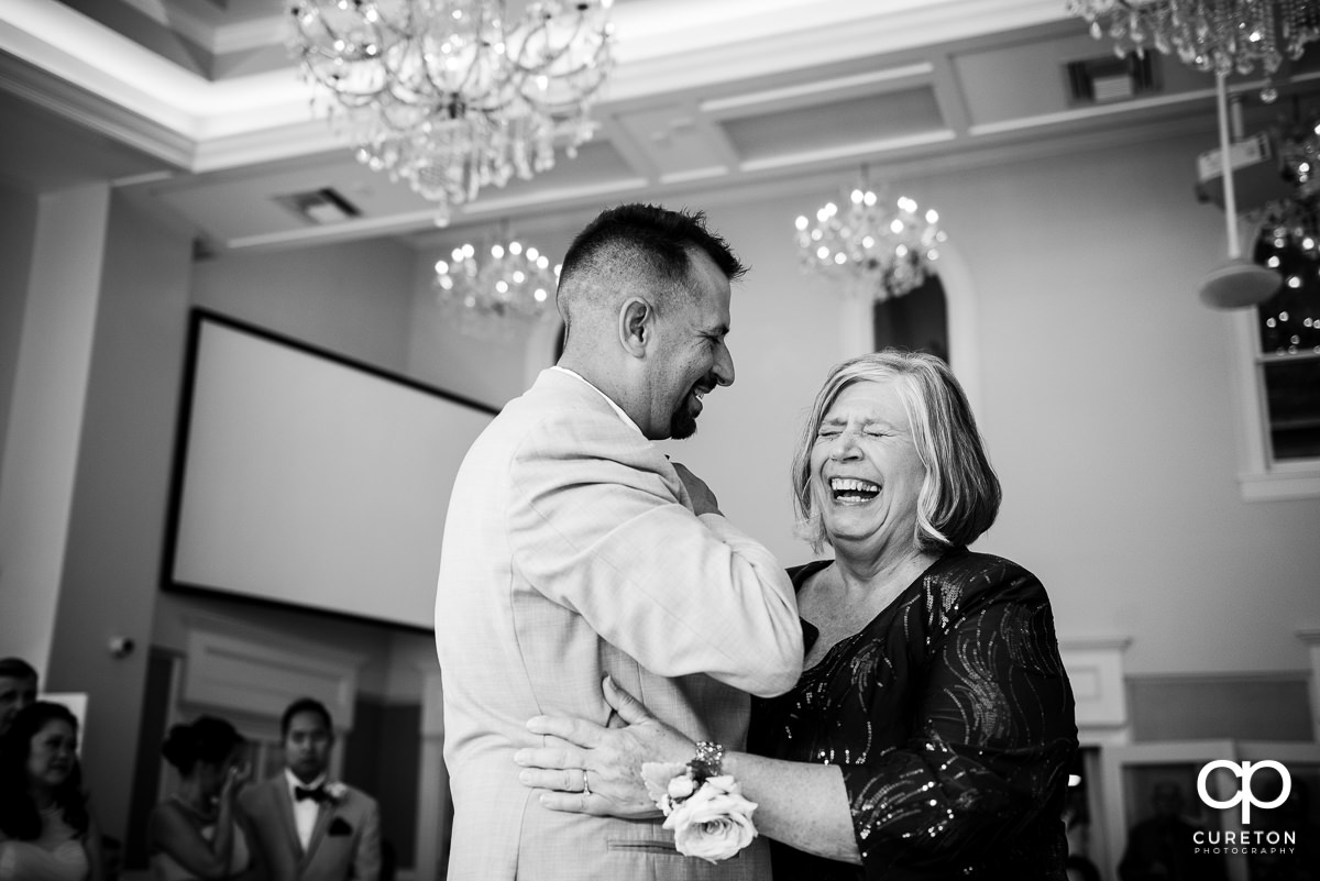 Groom's mother laughing during their dance at the reception.