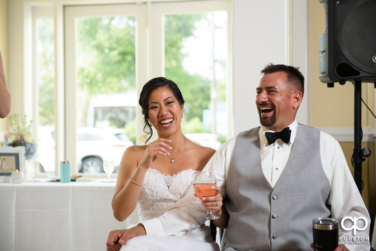 Bride and groom laughing during the maid of honor's speech.