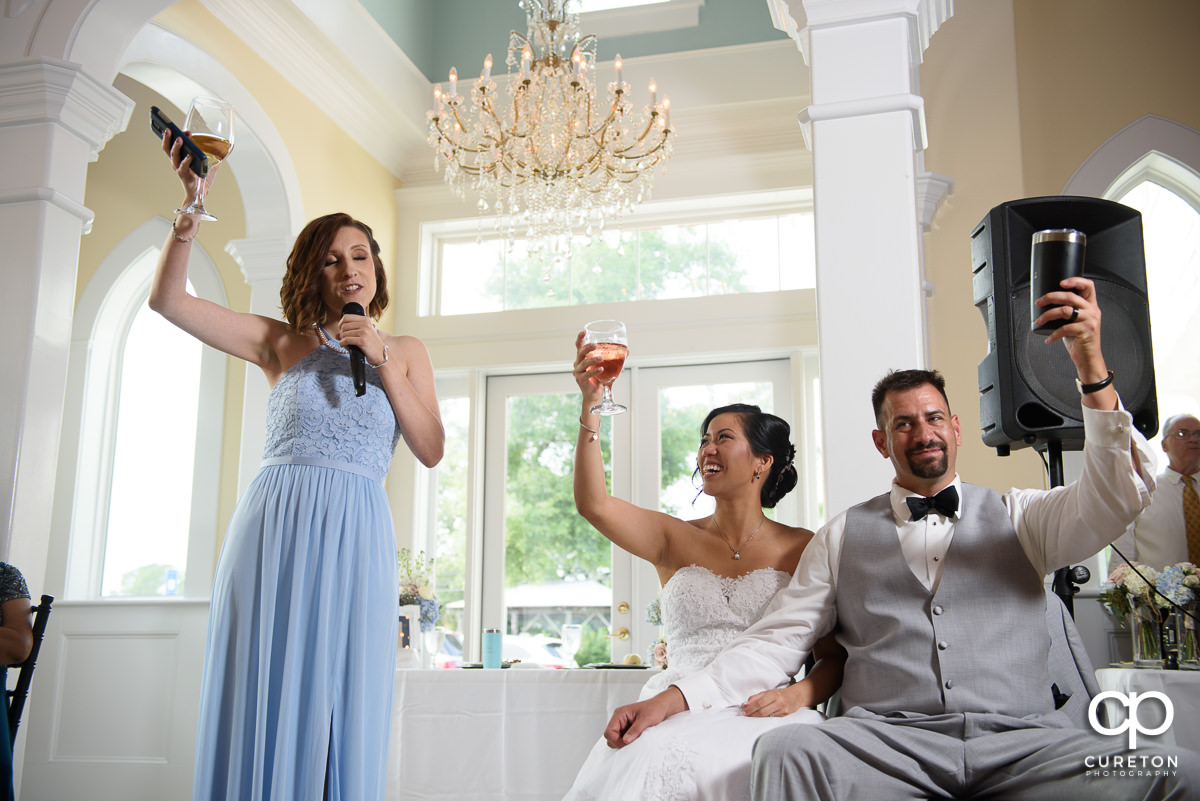 Bride, groom, and maid of honor holding up a glass to toast.