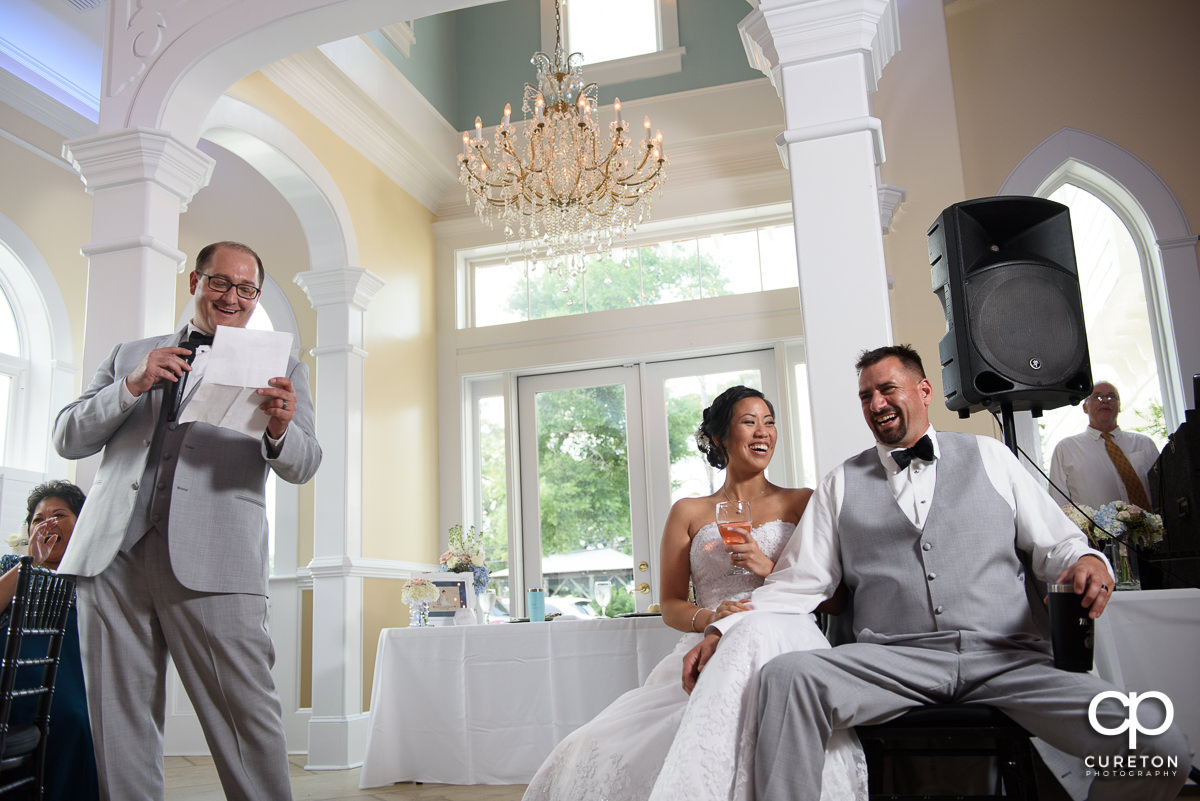 Couple laughing as the best man gives a speech.