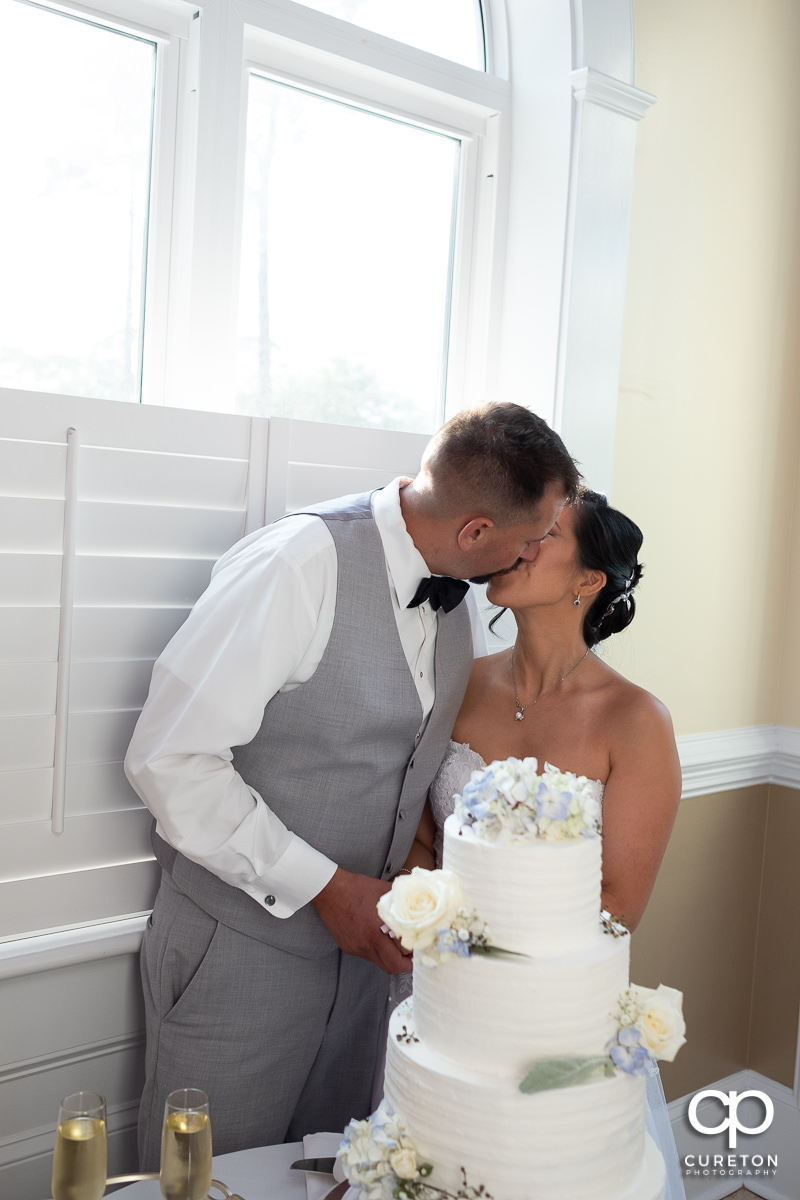 Bride and groom kissing while they cut the cake.