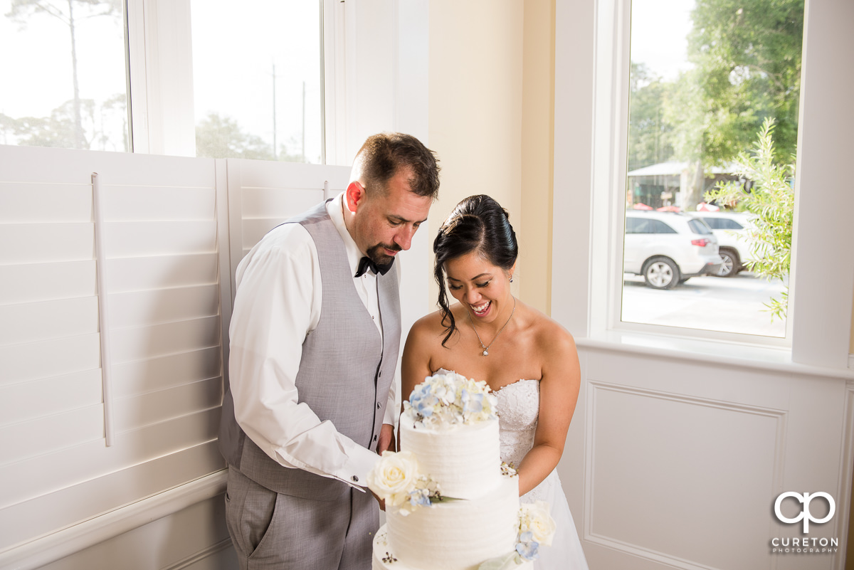 Bride and groom cutting the cake at the Tybee Island Wedding Chapel.
