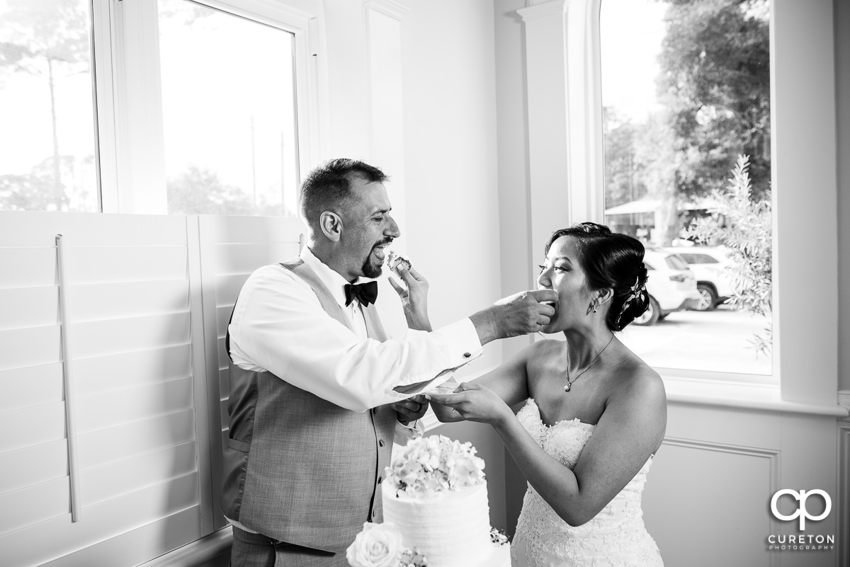 Bride and groom feeding each other cake.
