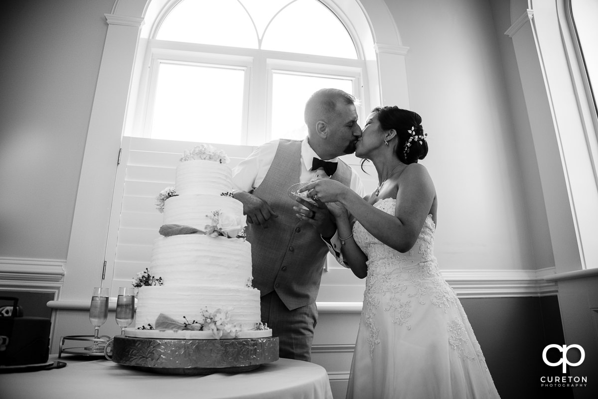 Married couple kissing at the wedding cake.