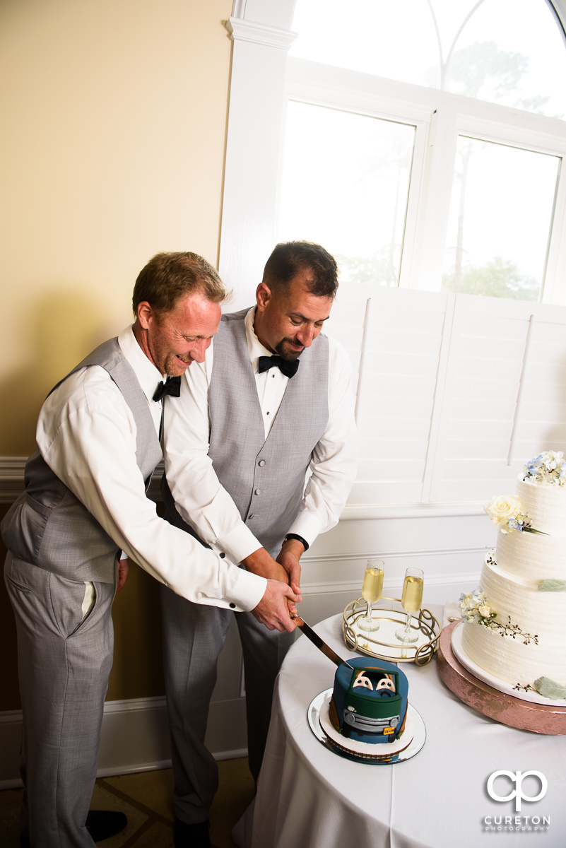 Groom and friend cutting the groom's cake.