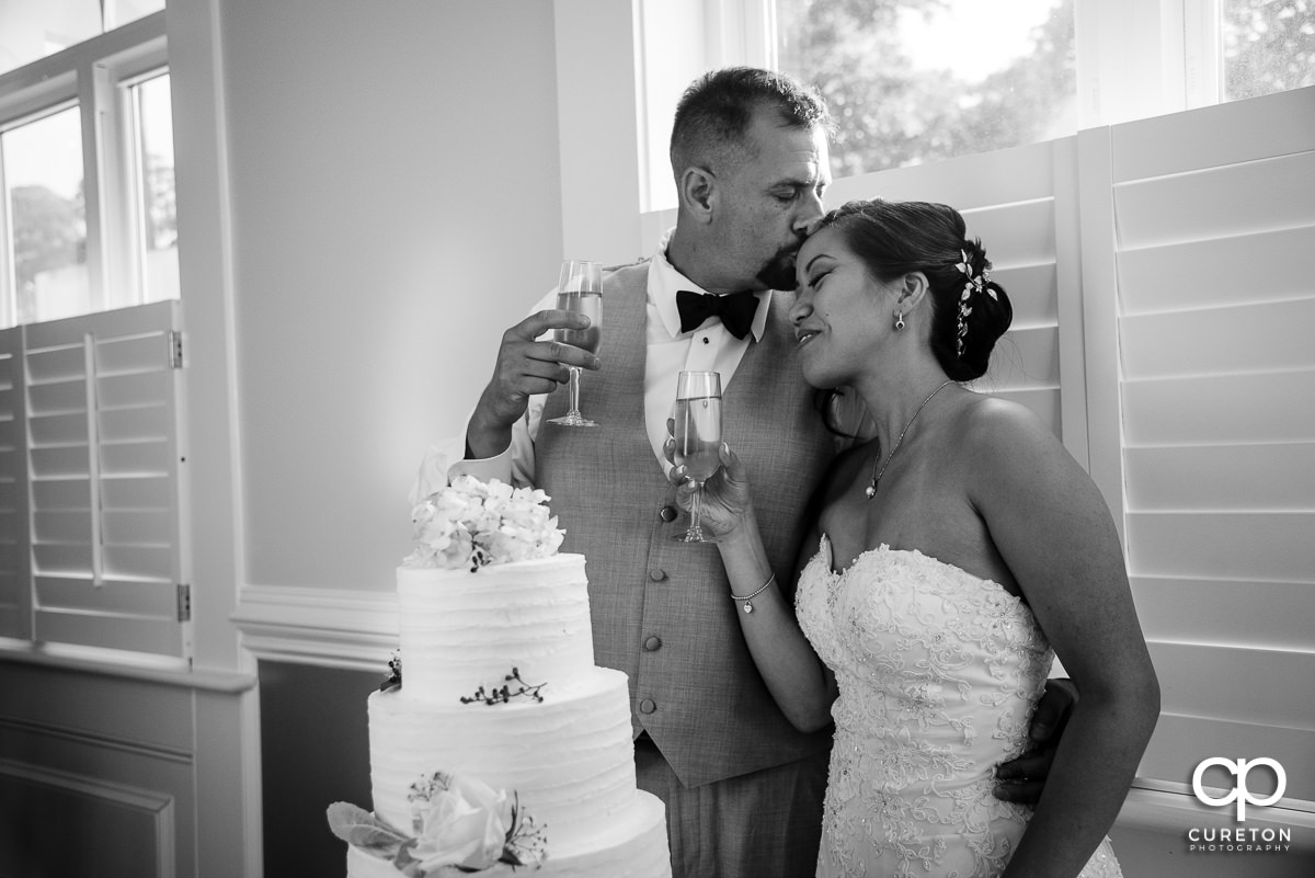 Groom kissing his bride on the forehead after cutting the wedding cake.
