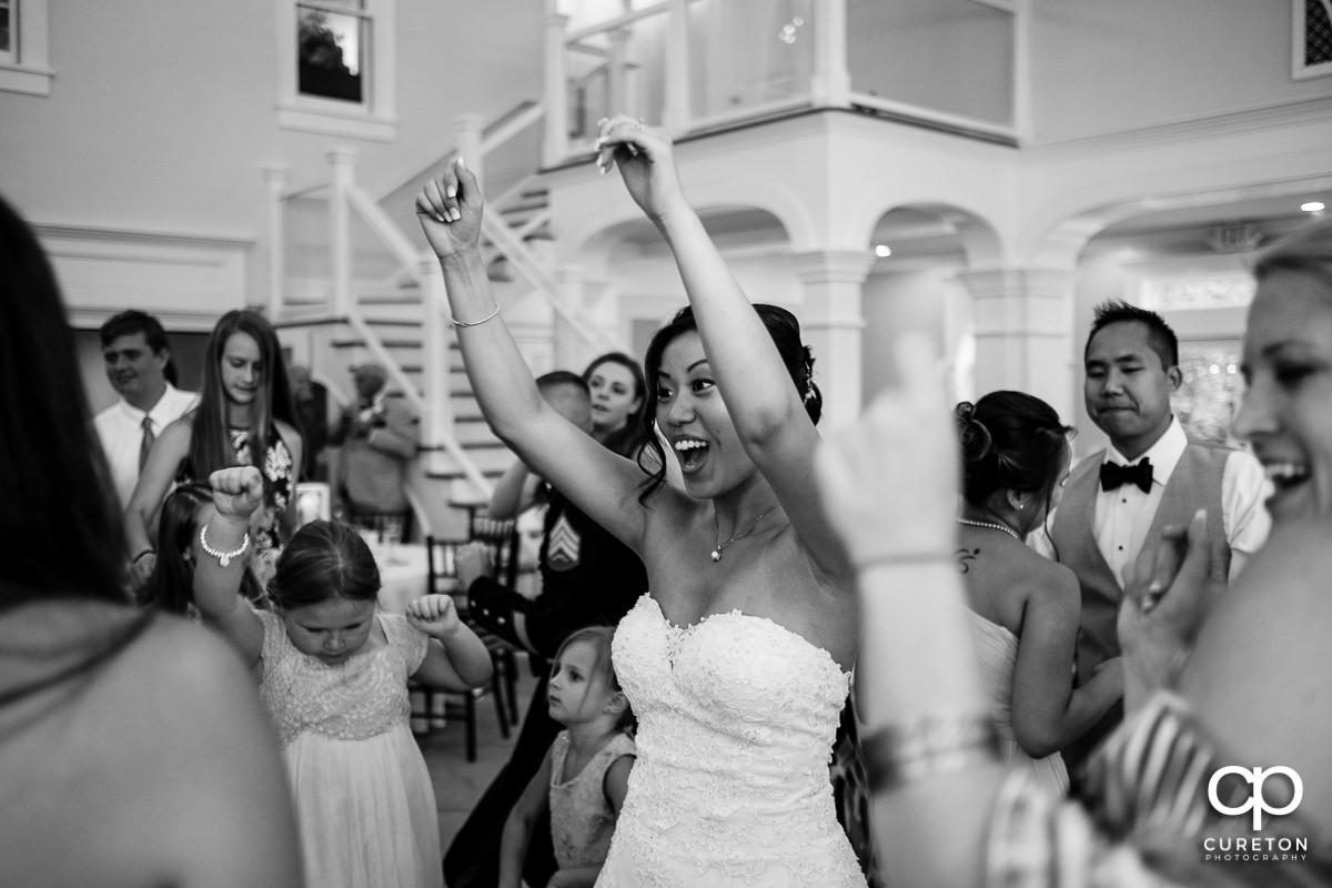 Bride dancing with hands in the air at the wedding reception.