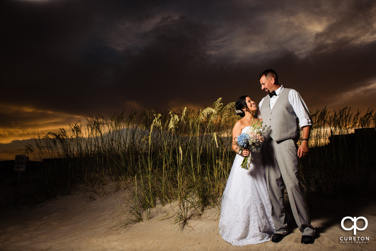 Bride and groom on Tybee Island beach at sunset after their wedding.