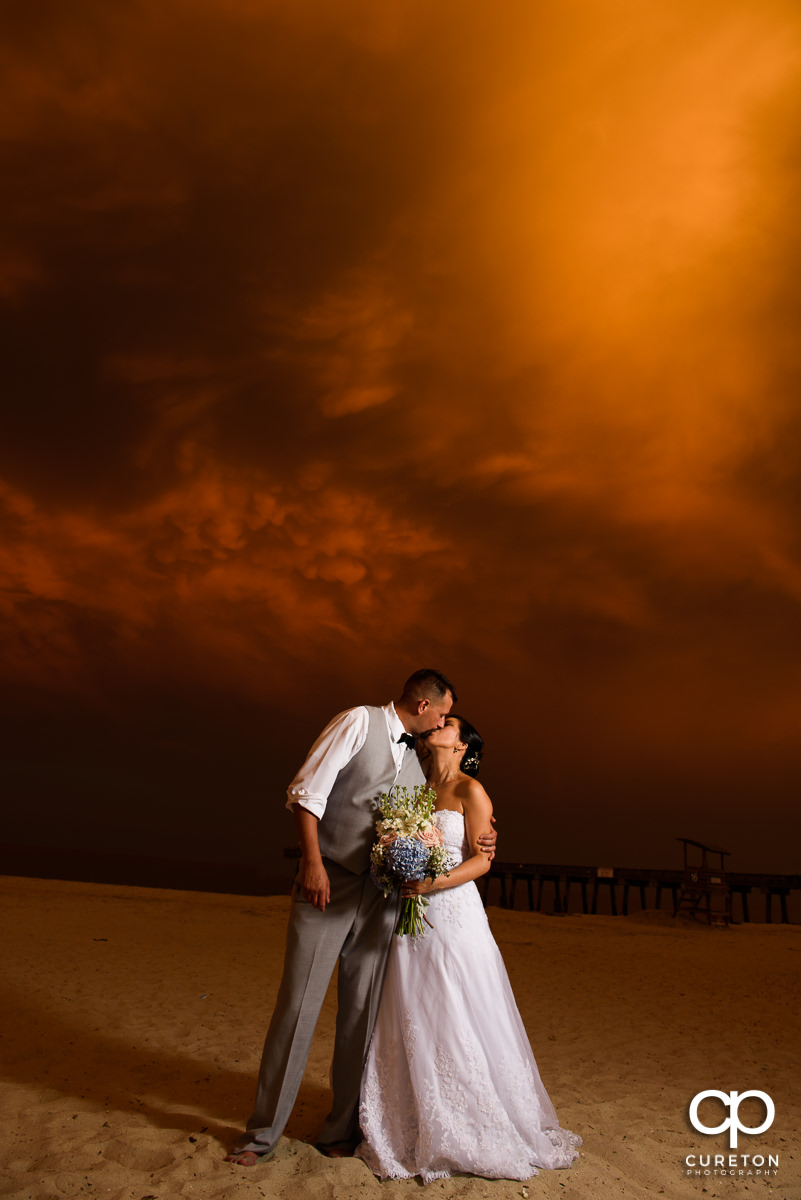 Bride and groom walking on the beach at sunset after their Tybee Island wedding.