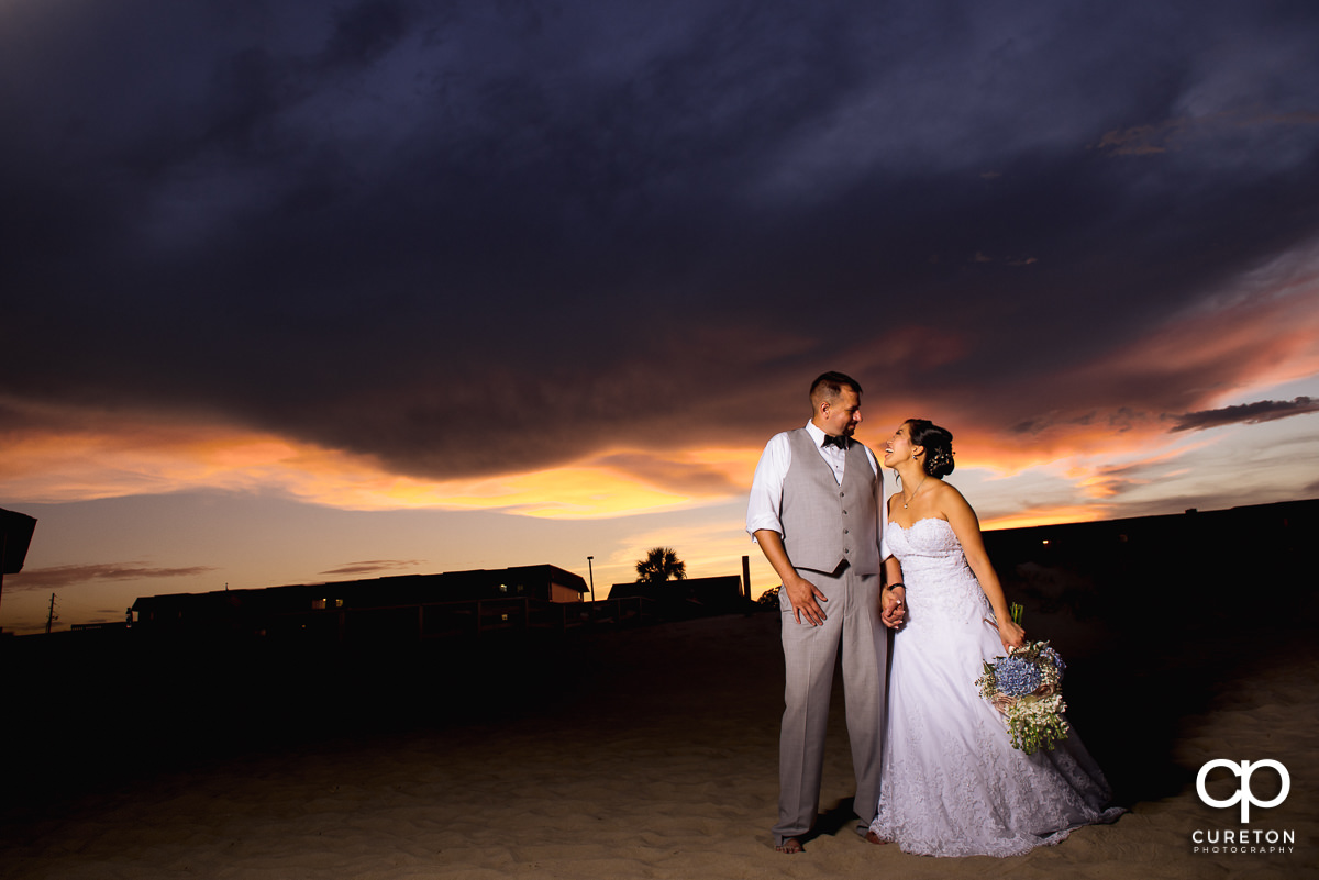 Bride and groom laughing at sunset on the beach.