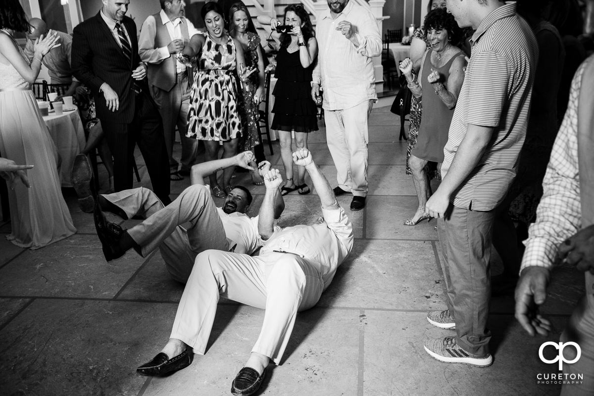 Groom and one of his friends on the floor dancing.