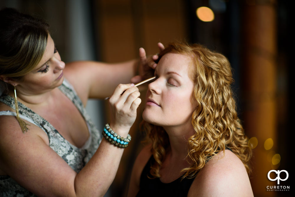 Bride getting her makeup did.