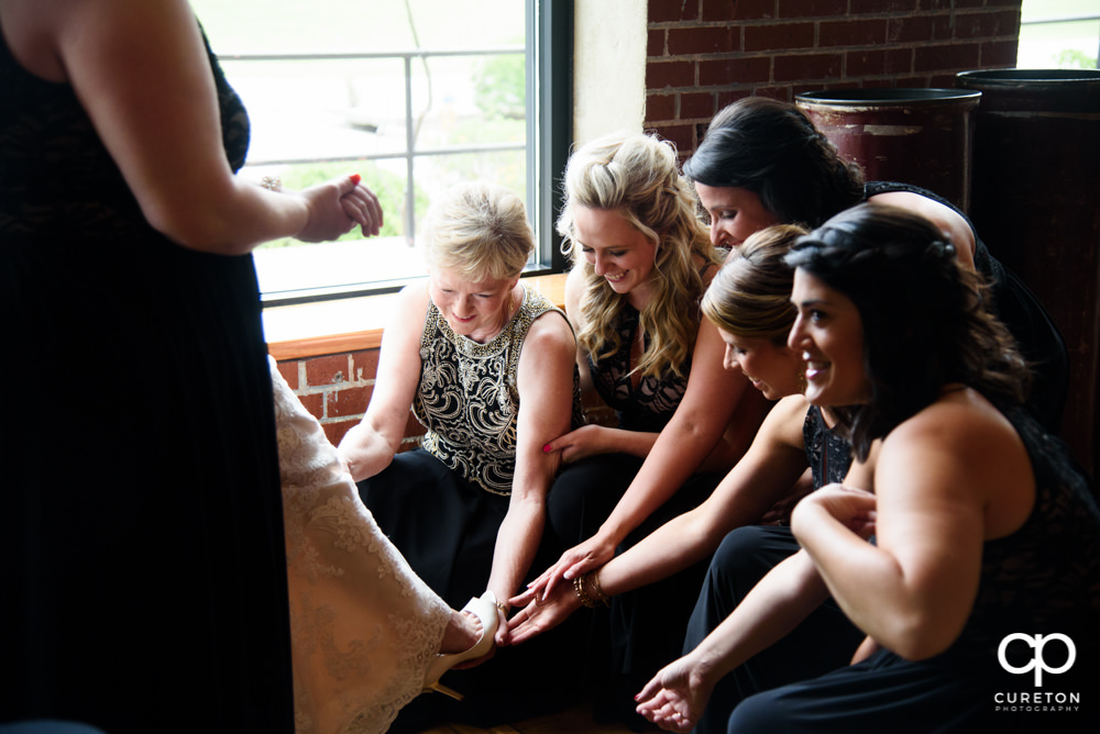 Bride's mom and bridesmaids helping the bride with her shoes.