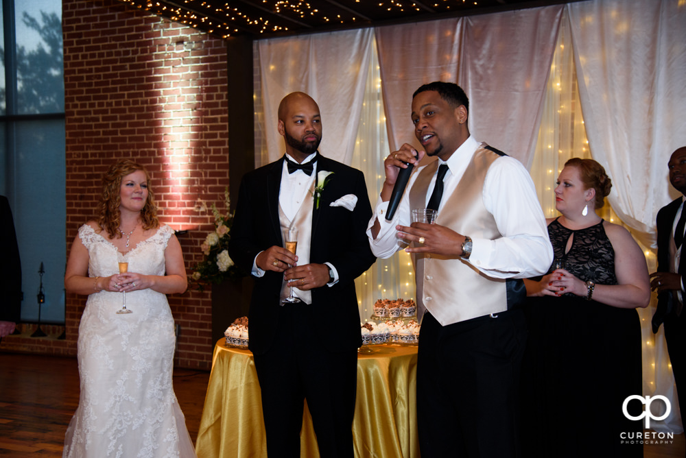 The wedding party gives a toast to the bride and groom.