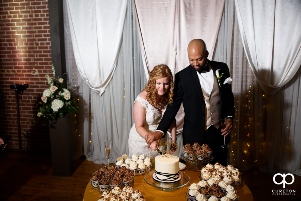 Bride and groom cutting the cake from Buttercream Bakehouse in Greenville,SC.