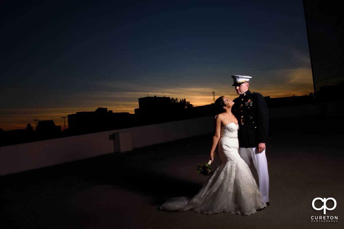 Bride and Groom on a rooftop in downtown Greenville at sunset after their wedding.
