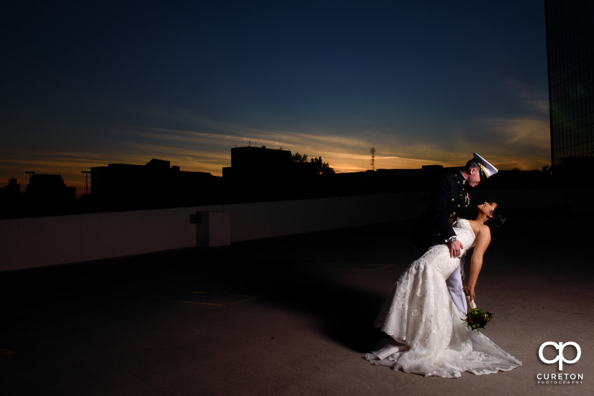 Groom dipping his bride at sunset.