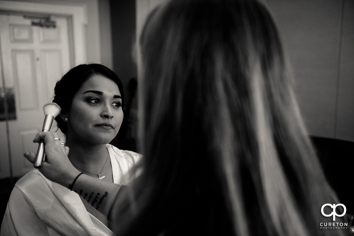 Bride getting makeup applied before the ceremony.