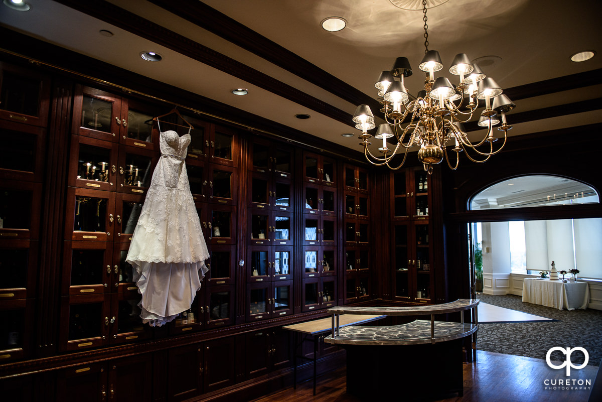 Bride's dress hanging in the wine room at The Commerce Club before the wedding.
