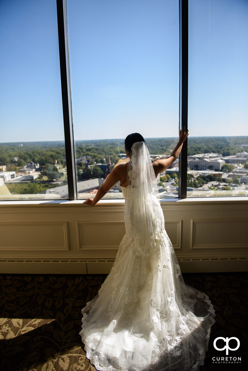 Bride standing in the window at The Commerce Club before the ceremony.