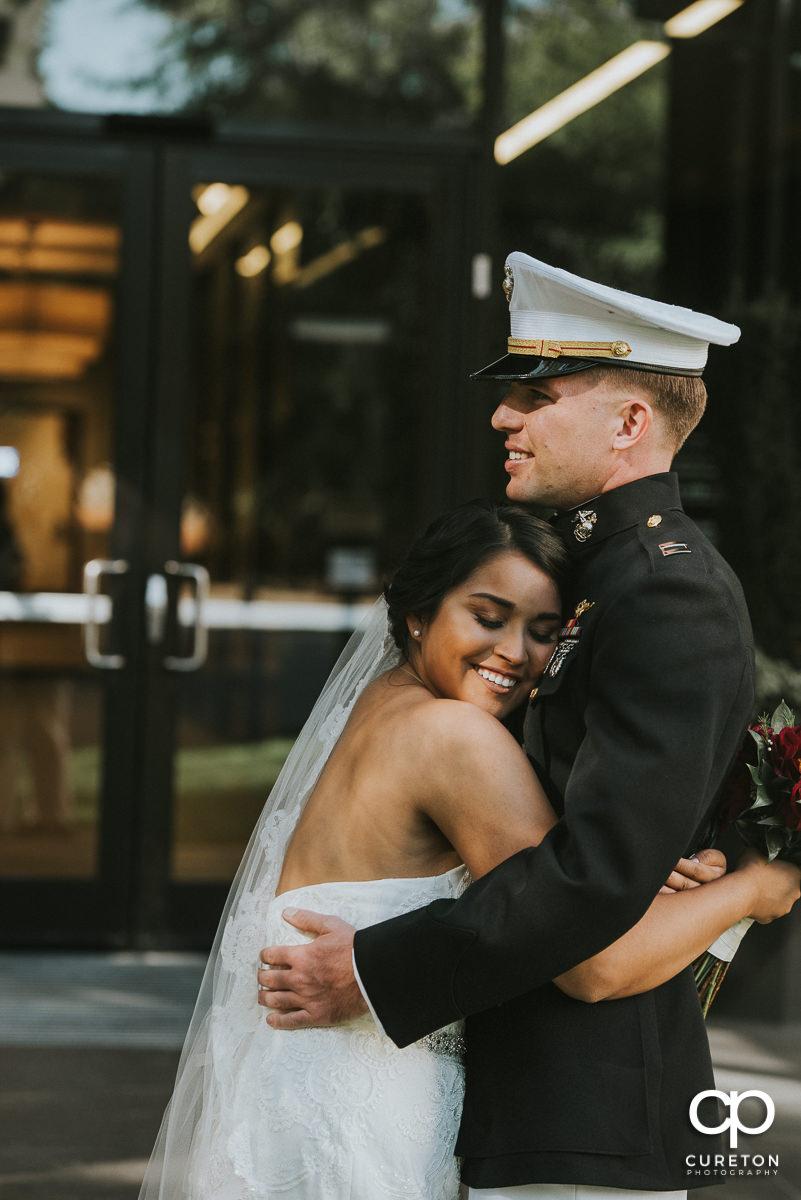 Bride hugging her groom in Marine dress uniform.