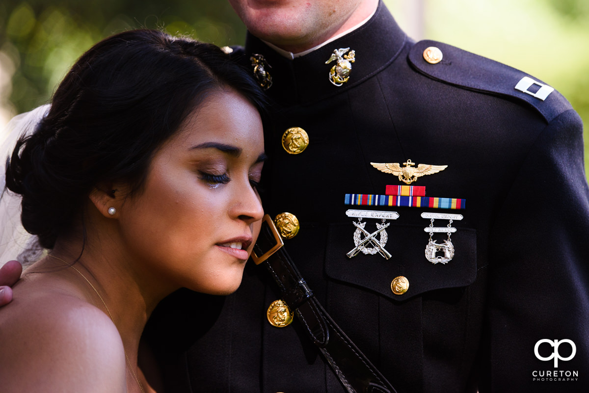 Bride crying on the chest of her groom in military uniform during a first look.