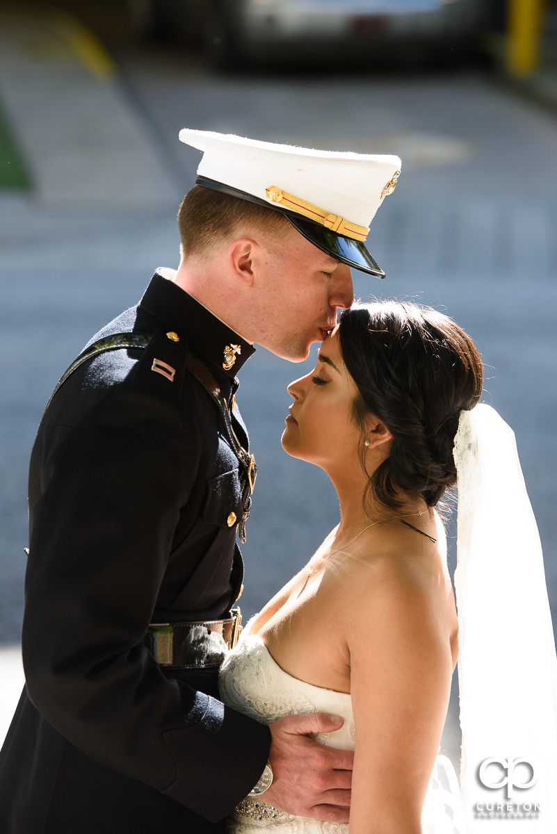 Groom kissing his bride on the forehead.