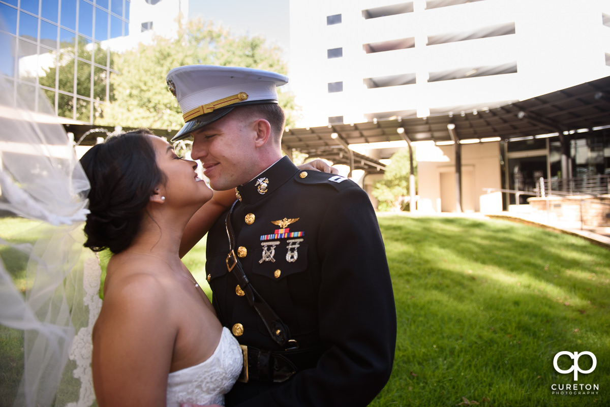 Bride and groom kissing with the veil blowing in the wind.