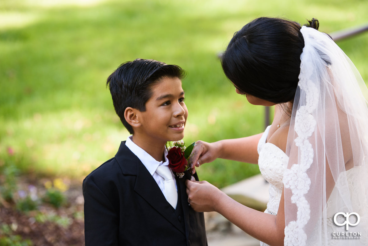 Bride putting a flower on her son.