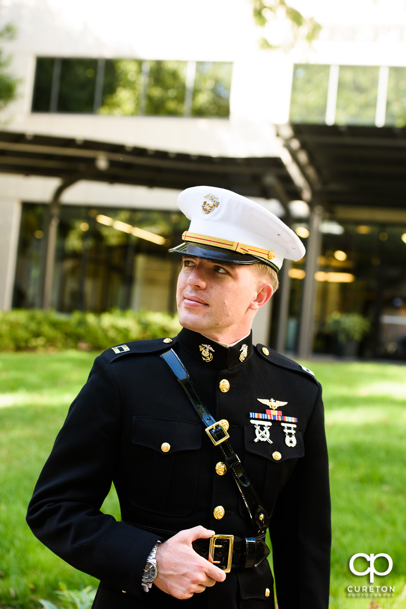 Groom in military uniform in front of the Commerce Club.
