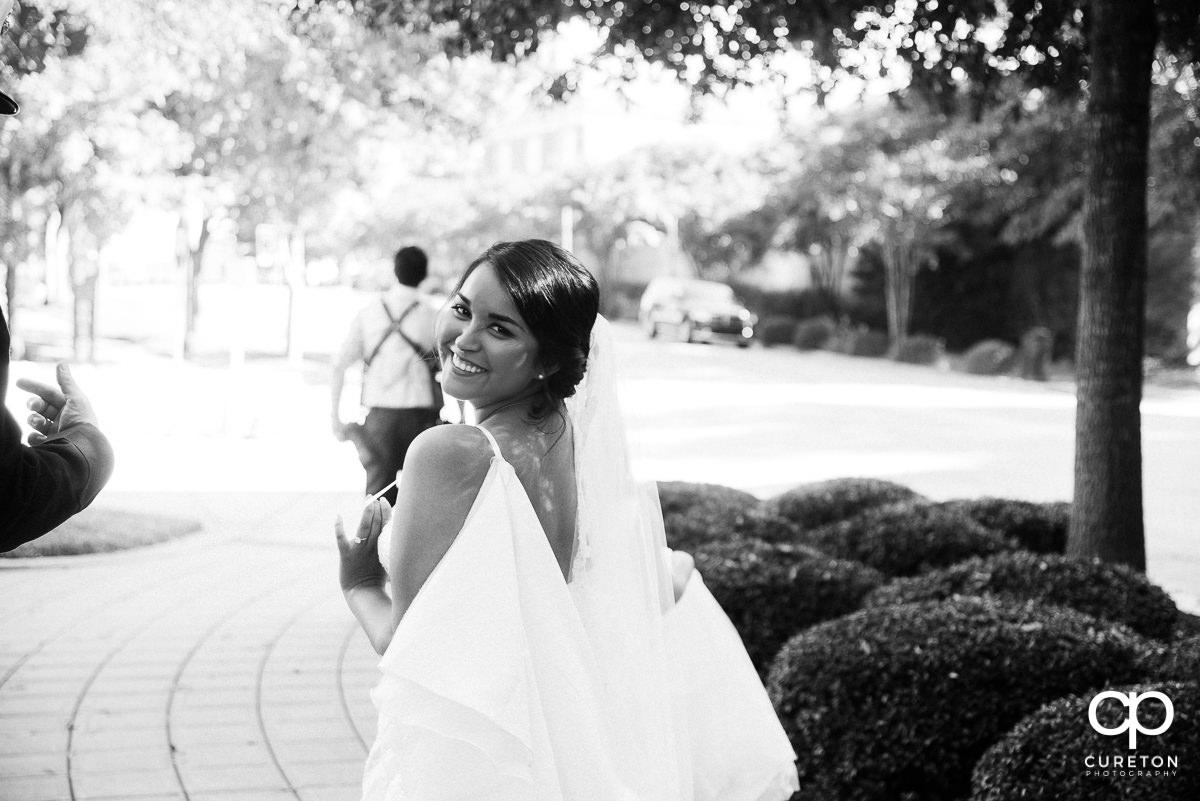 Bride looking back walking dow a sidewalk in downtown Greenville,SC.