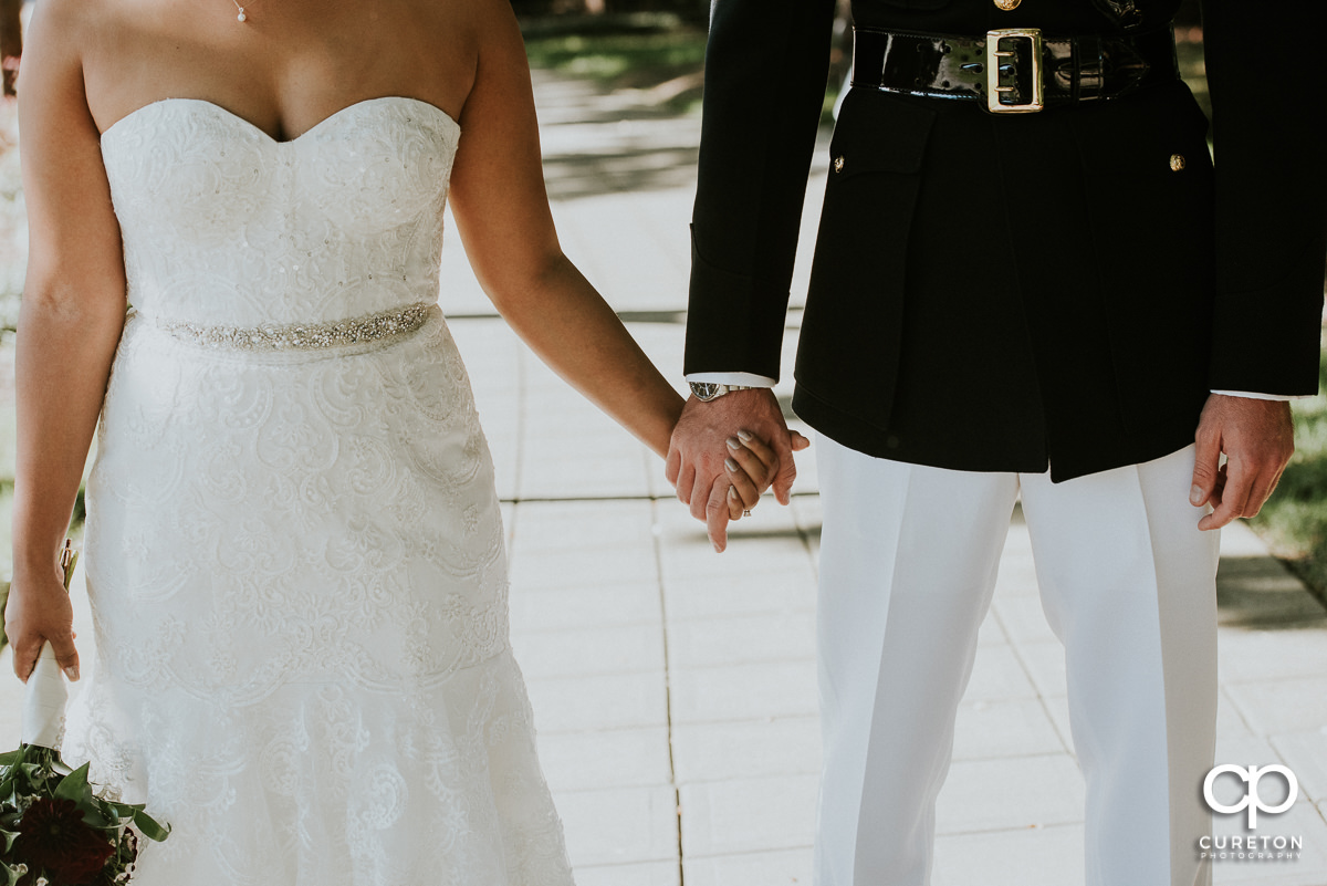 Bride and groom holding hands closeup.