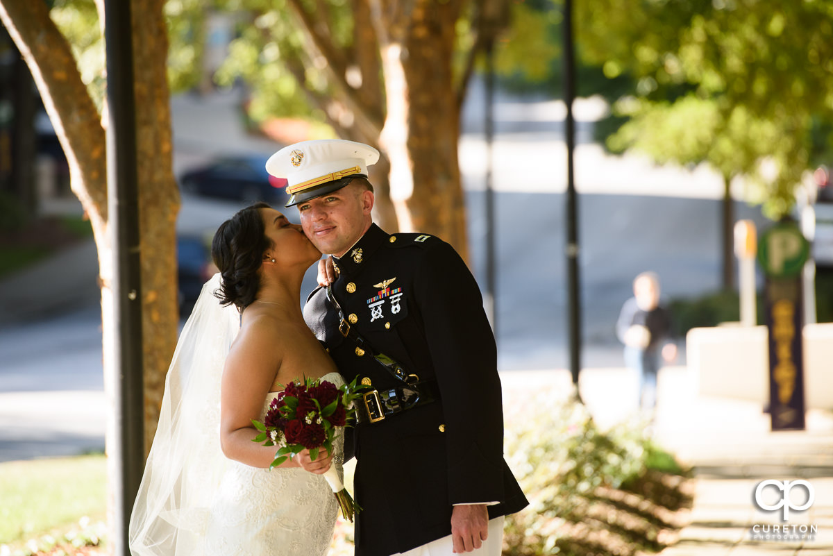 Bride kissing her groom on the cheek.