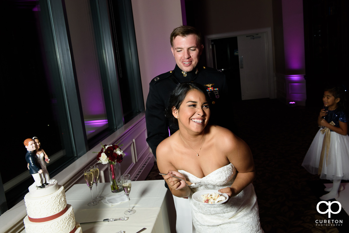 Bride laughing at the cake cutting.