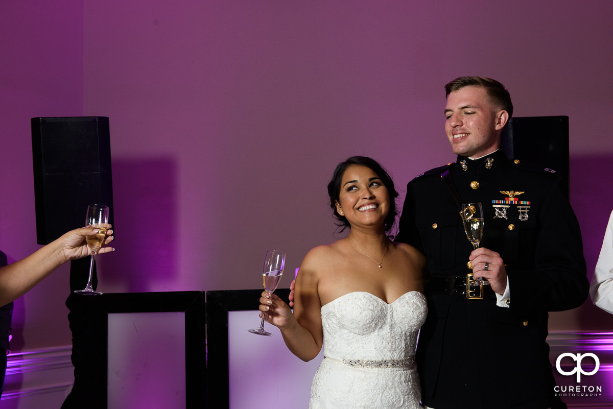 Bride smiling while her mother gives a toast.