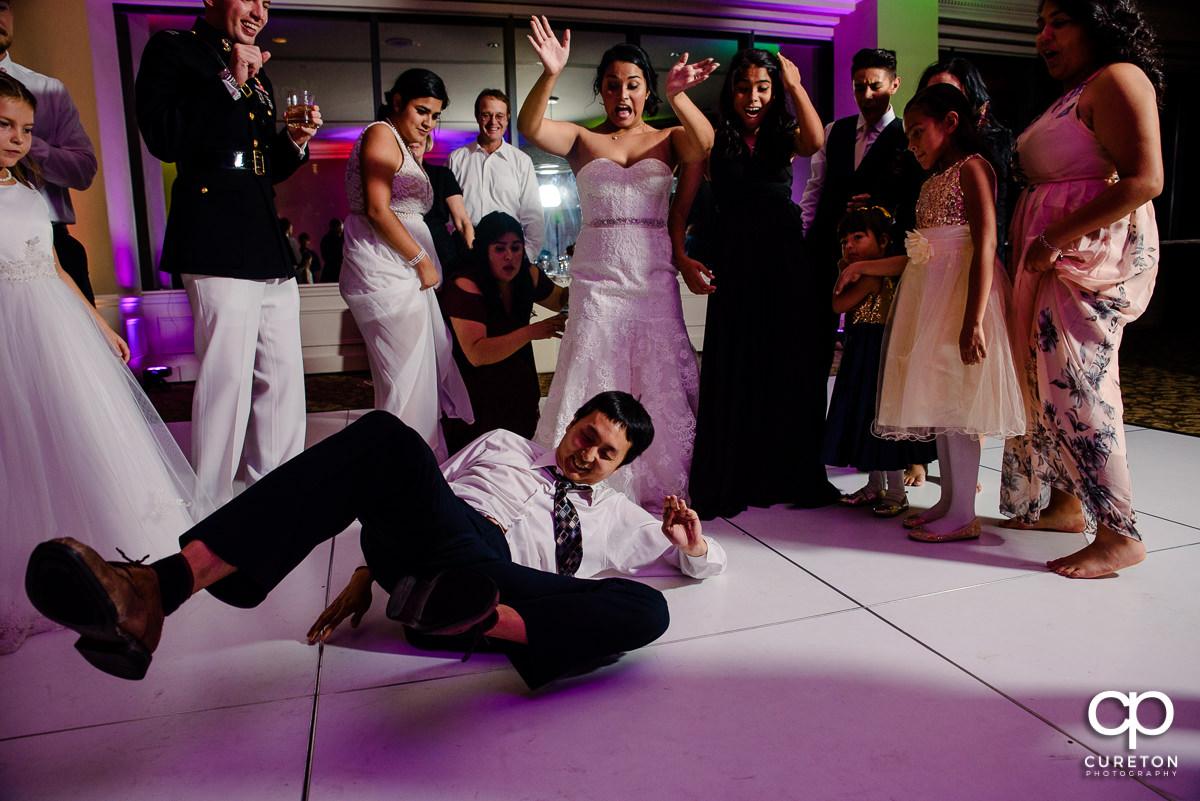 Bride cheering as a wedding guest break dances at the reception.