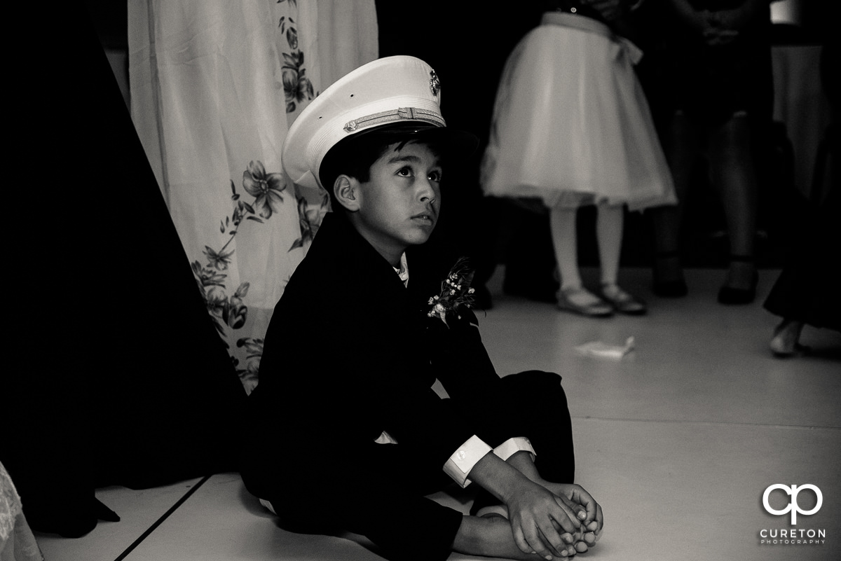Ring bearer wearing the grooms military dress hat.