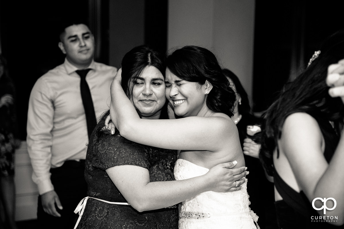 Bride getting emotional with her mother at the wedding reception.
