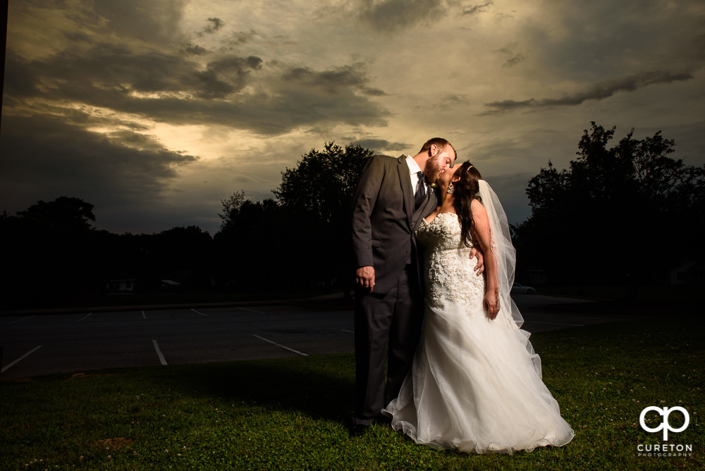 Bride and Groom kissing at sunset after their wedding at The Loom a venue in Simpsonville, SC.