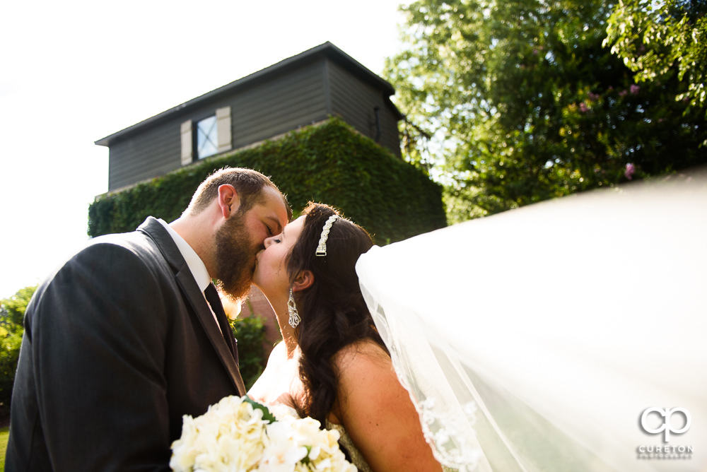 Bride and groom kissing withe her veil blowing in the wind after their wedding at The Loom a venue in Simpsonville, SC.